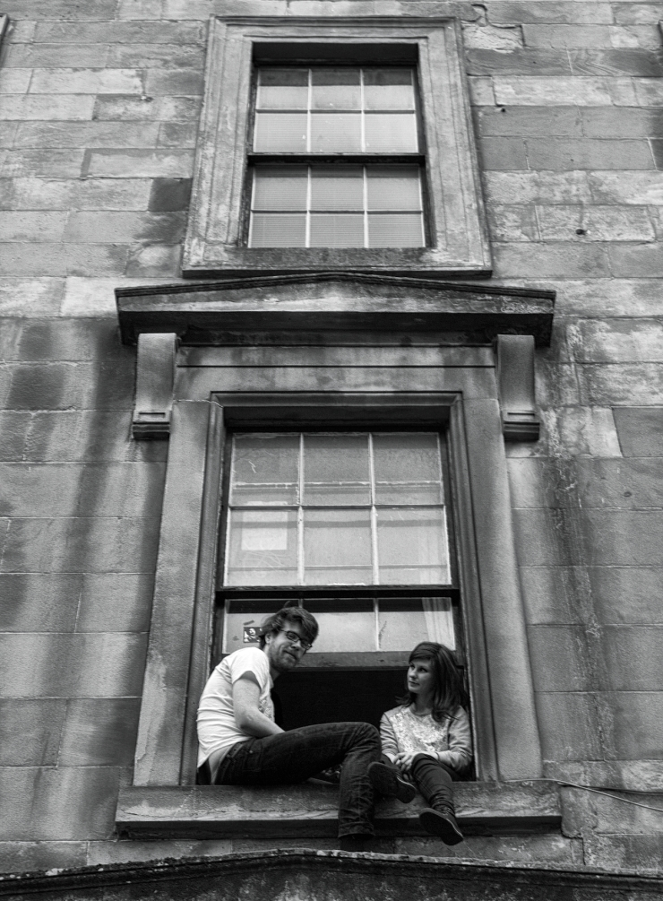 View of a couple sitting at their windowsill in Garnethill of a Sunday