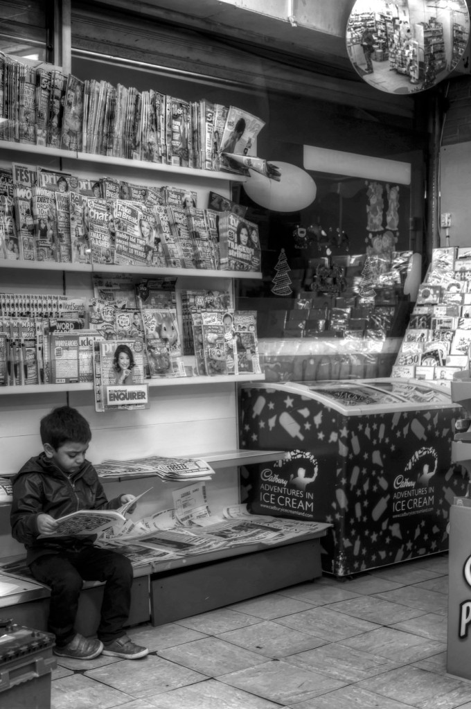 A small child reads on in a newsagent shop in the port of Leith